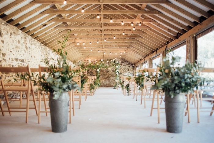 The-inside-of-the-Cowyard-Barn-rustic-party-and-reception-space-set-for-a-wedding-ceremony-at-Pengenna-Manor-Cornwall-wedding-venue-1-700x468